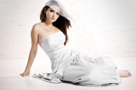 Una bella giovane donna in bridalwear in uno studio di bianco con il vento nei capelli.