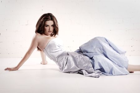 A beautiful young woman sitting in a white room in a glamorous dress. photo