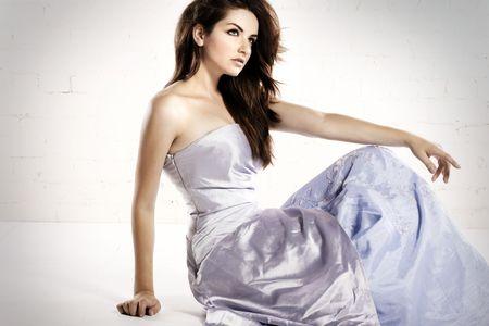 Una bella giovane donna seduta in una stanza bianca in un vestito di glamour. Archivio Fotografico