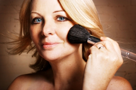 A beautiful middle aged woman applying blusher and looking at the camera. photo