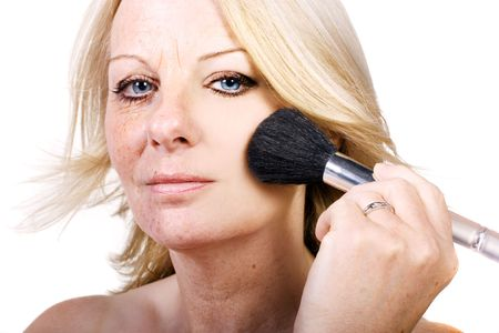 A close up of a middle aged woman using a blusher brush and her flaws are magically disappearing. photo