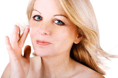 Una bella donna et� centrale applicando la crema per il viso.