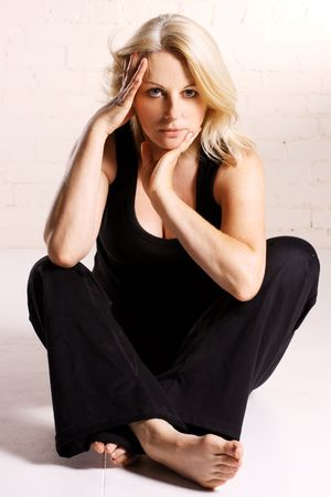 A beautiful blond middle aged woman wearing black in a white studio. photo