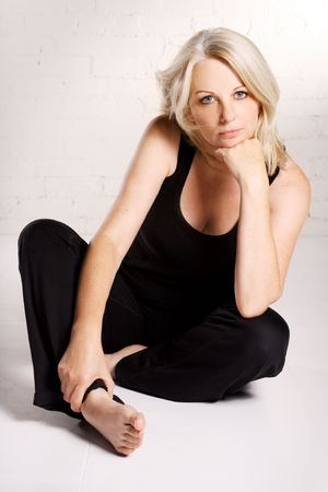 A beautiful blond middle aged woman wearing black in a white studio. Stock Photo - 7561822