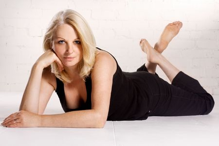A beautiful blond middle aged woman wearing black in a white studio.