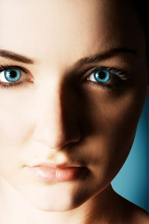 A moody closeup of a young woman with very blue eyes, on a blue background.