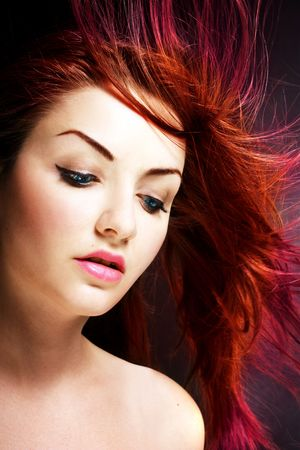 A young woman with her multicolored hair blowing in the wind.