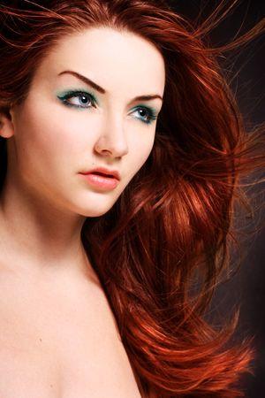 tinte cabello: Un disparo de la belleza de una mujer joven de ojos azul con su pelo rojo que fluye en el viento.  Foto de archivo