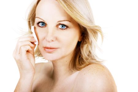 A gorgeous middle aged woman removing her make up with a cotton wool pad on a white background. photo