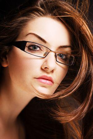 Una donna piuttosto giovane, indossando occhiali moderni con il vento nei capelli.  Archivio Fotografico