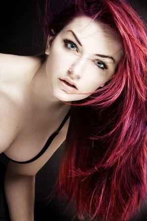Una donna con i capelli magenta guardando la fotocamera davanti a uno sfondo scuro.
