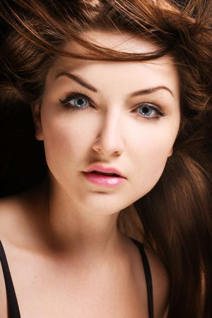 brown hair blue eyes: A beauty shot of a young blue eyed woman with her brown hair flowing in the wind.