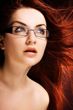 A pretty young woman wearing modern glasses with wind in her hair. photo