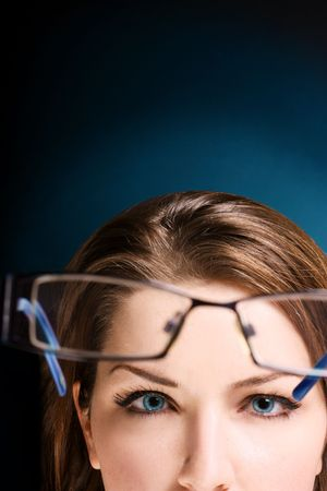 upper half: The upper half of a womans face looking at her glasses. Space for text.