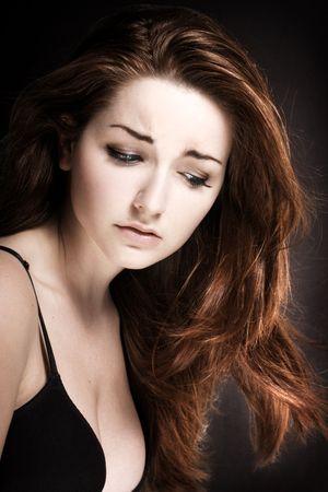 persona deprimida: Un joven deprimido mujer delante de un fondo negro.  Foto de archivo