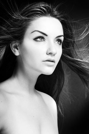 A beauty shot of a young blue eyed woman with her hair flowing in the wind. Black and white. photo