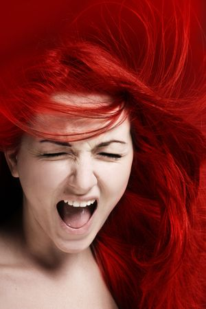 A furious young woman with her hair red like fire.