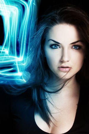 Una donna molto giovane con una luce blu luminoso vicino al suo viso. Ritratto surreale.  Archivio Fotografico
