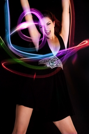 cabello casta�o claro: Una joven mujer bailando con luces vibrantes alrededor de ella. Luz de pintura.