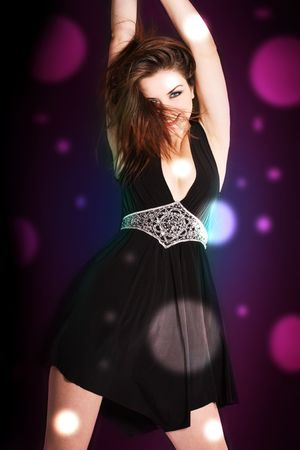 A pretty young woman disco dancing in a club with bright lights. Stock Photo - 7736195