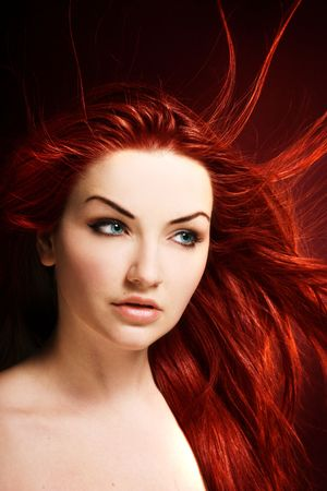 A beauty shot of a young blue eyed woman with her red hair flowing in the wind. Foto de archivo