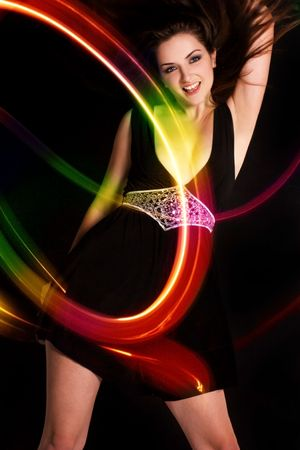 A young woman dancing with vibrant lights around her. Light painting. photo