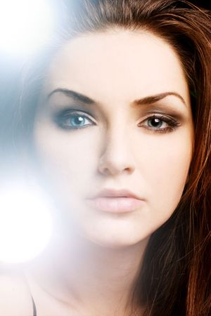 brown hair blue eyes: A pretty young woman with an illuminous glowing lights near her face. Beauty shot.