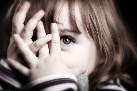 Una bambina meravigliosa giocando peekaboo e peering attraverso le dita. Adorabile.