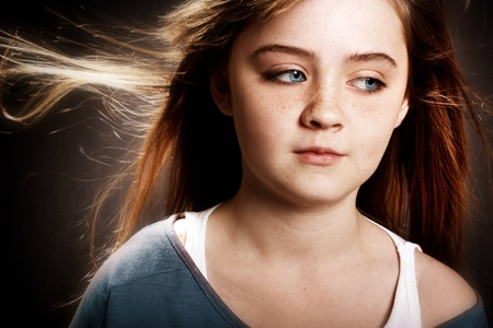 A beautiful young girl with her hair blowing in the wind. photo