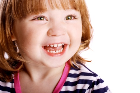 An adorable little girl laughing in front of a white background.