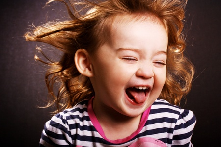 An adorable little girl laughing with wind in her hair.