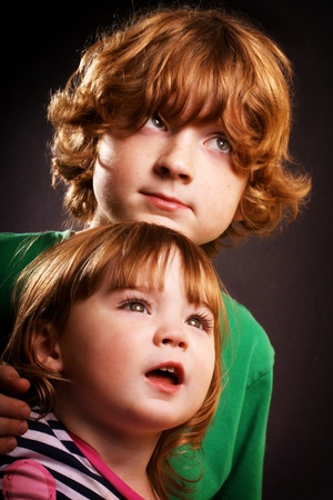 An adorable brother and sister in front of a black background. photo