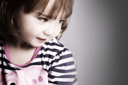An adorable little girl looking to the light in front of a black background. photo