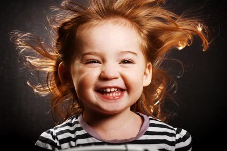 Una splendida bambina sorridente istericamente con il vento nei capelli. Archivio Fotografico