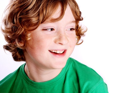 young boy smiling: A cute young boy smiling in front of a white background.