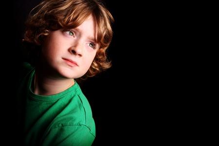 bambini pensierosi: Un giovane ragazzo carino guardando in alto su sfondo nero.