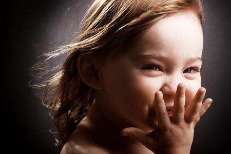 Una bellissima bambina risa istericamente con il vento nei capelli. Archivio Fotografico