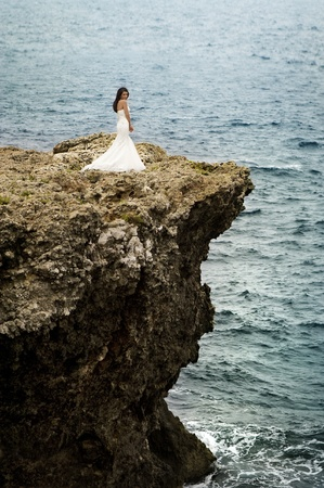 A beautiful bride standing on a cliff on the sea  photo