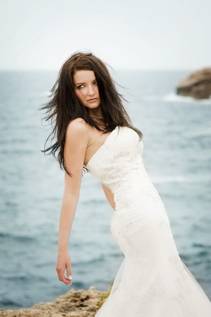 adult mermaid: A beautiful bride on the coast looking away