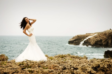 adult mermaid: A beautiful bride standing on a cliff on the sea