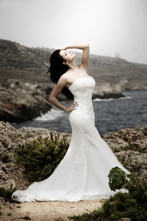 Beautiful bride posing on the coast with angelic lighting photo
