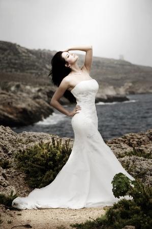 sexy bride: Beautiful bride posing on the coast with angelic lighting Stock Photo