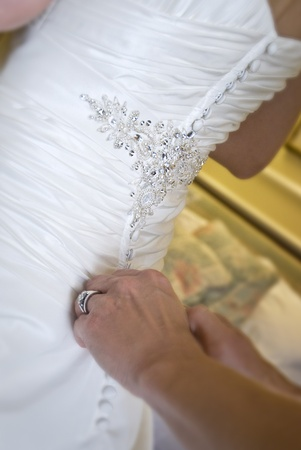getting ready: Bride being buttoned