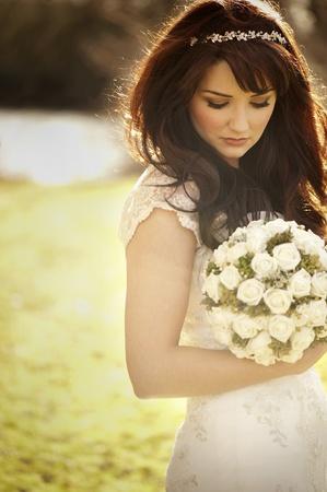 auburn: Vintage bride outdoors with bouquet Stock Photo