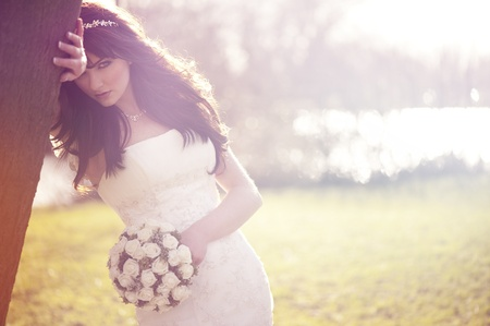 A beautiful bride looking at the camera outdoors.