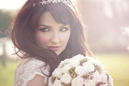 A beautiful bride looking to the side outdoors  photo