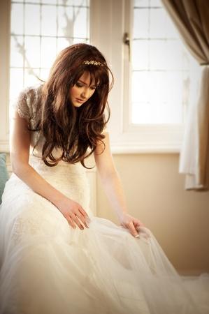vistiendose: Una novia hermosa ajustar su vestido de novia