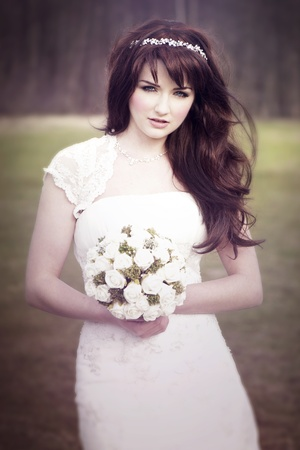 auburn: A beautiful bride looking at the camera outdoors.