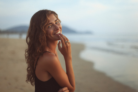 gratified: Portrait of a young beautiful woman with long curly hair at the seaside under the evening sunset
