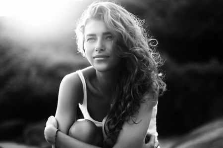 gratified: Black and white portrait of a young beautiful woman with long curly hair at the seaside under the evening sunset Stock Photo